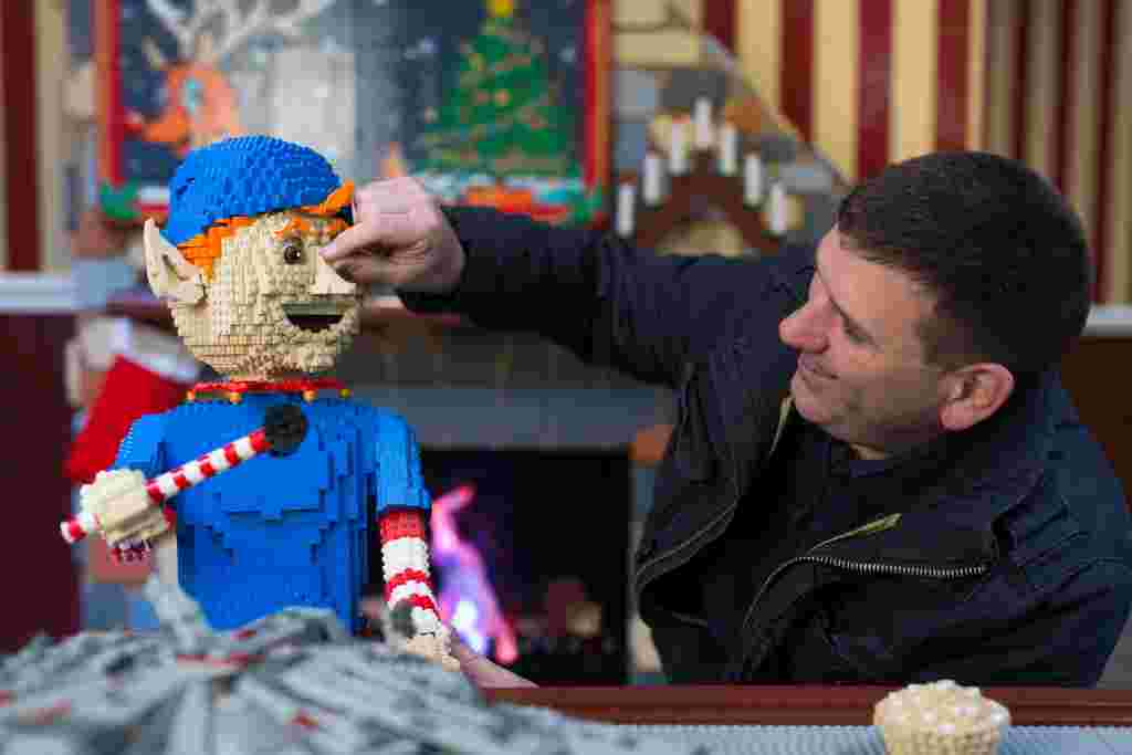Duncan Titmarsh the UK's only LEGO Certified Professional Builder puts the finishing touches to the LEGO Santa's Workshop in Covent Garden. Photography David Parry/PA Wire