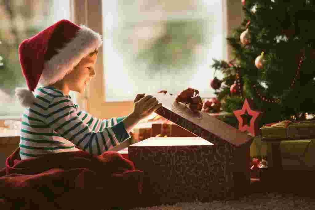 Little boy opening Christmas present, smiling and looking at shiny box.